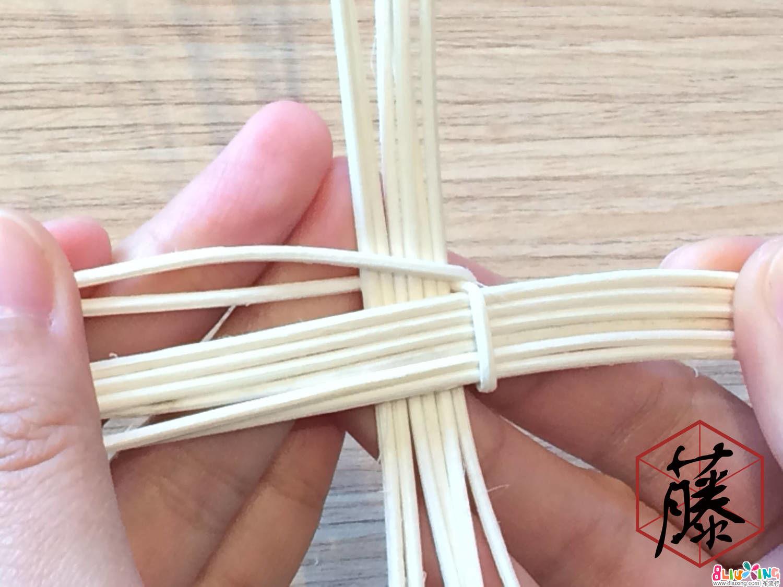 将处于前方的藤料往后绕过主枝,后方的藤料则往前绕过主枝。如此交叉编织,围中心绕两圈。