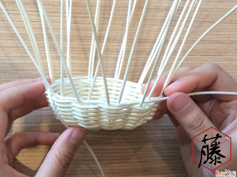 用其中一条藤料,一前一后绕过每条主枝编织。